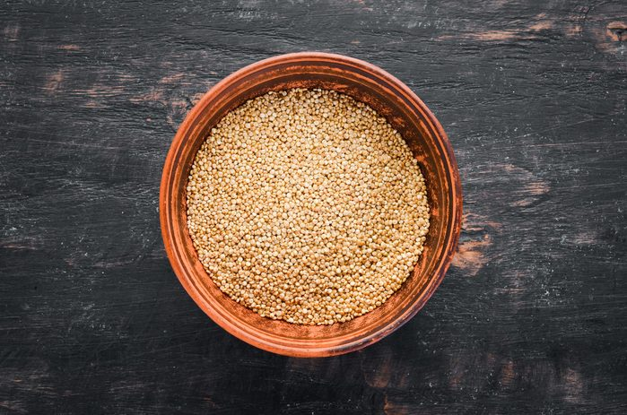 Foods everyone over 50 should be eating - Raw white quinoa. On a black background. Top view. Free copy space.