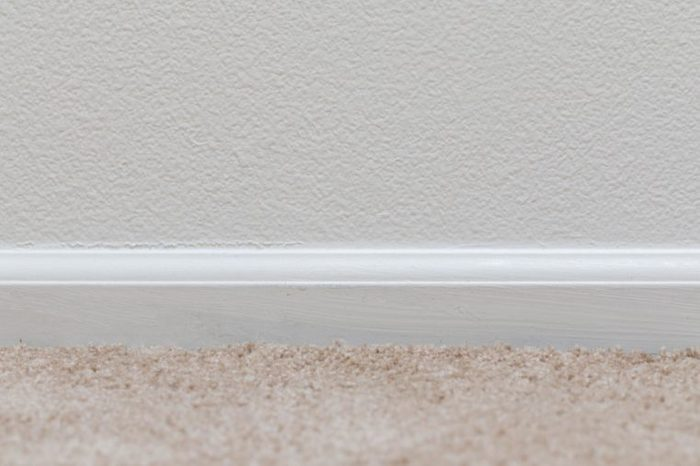 Basic floor trim up against a tan carpeted floor