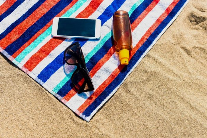 Beach Towel, mobile phone and sunscreen on the beach