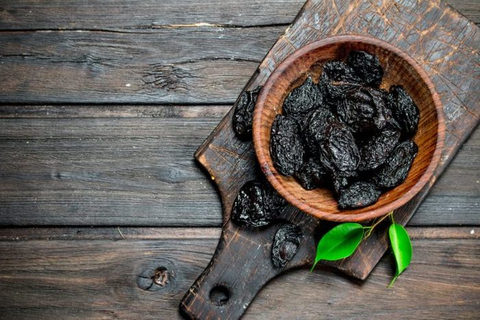 Prunes with green leaves in the bowl. On a wooden background.