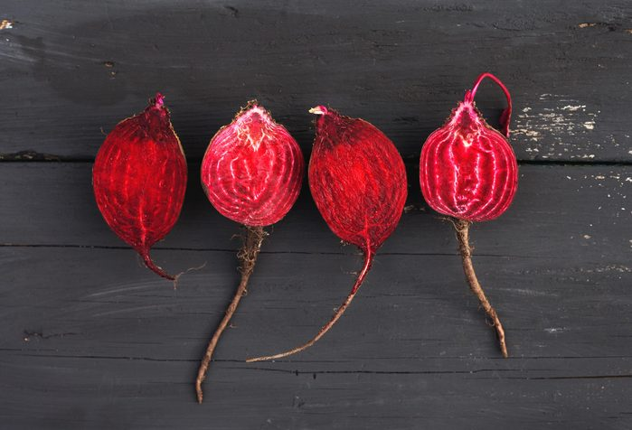 Foods everyone over 50 should be eating - Raw beet on black wooden background