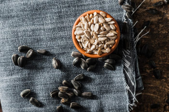 Foods everyone over 50 should be eating - Fresh Sunflower seed and oil. Shelled sunflower seeds in wood bowl. Sunflower close-up