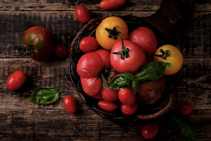 Foods everyone over 50 should be eating - Colourful tomatoes, red , yellow , orange , green on vintage wooden background