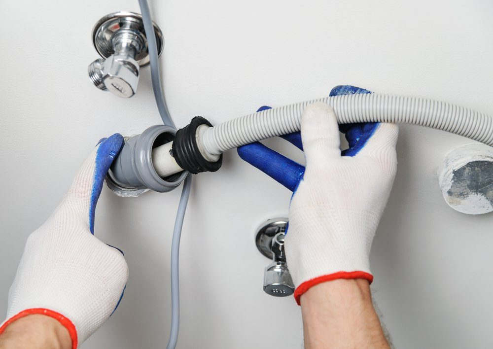Installation of household appliances. Workman attaches a drain hose to a sewage pipe.