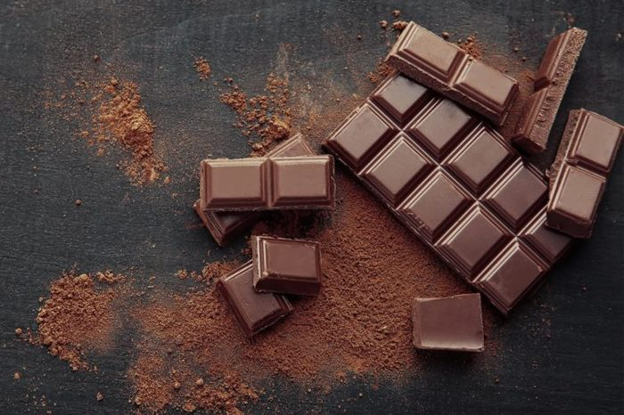 Broken chocolate pieces and cocoa powder on wooden background