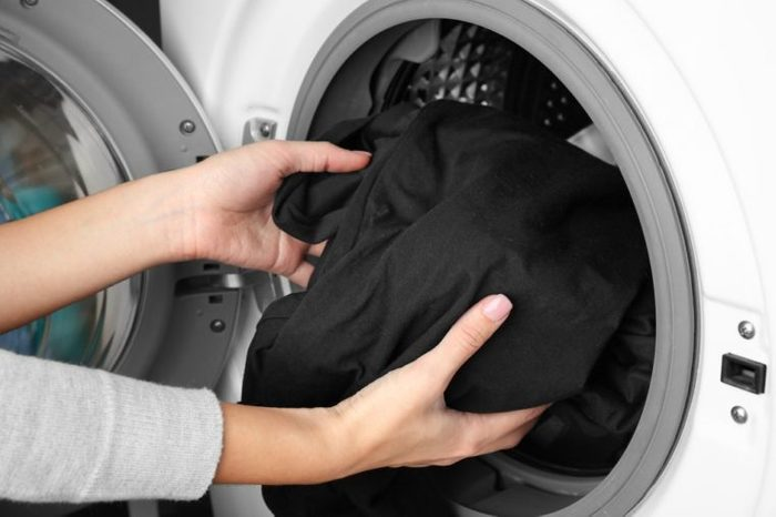 Female hands getting out clean clothes from washing machine