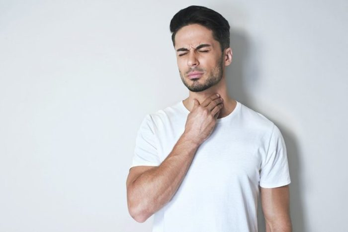 Young man having sore throat and touching his neck, wearing a loose white t-shirt against light grey background. Hard to swallow