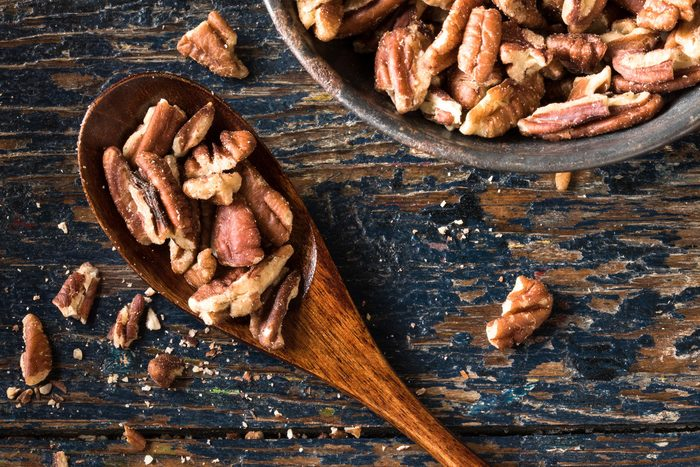 Foods everyone over 50 should be eating - Chopped pecans on a wood spoon