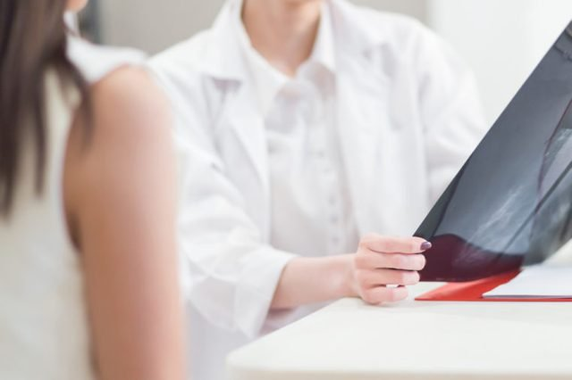 Female doctor holding the Mammogram film image and give advice her patient in consulting room.