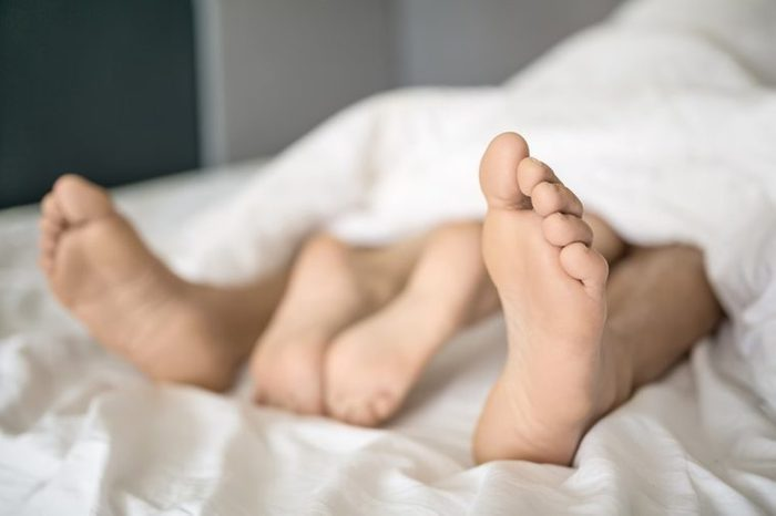 Closeup photo of the barefoot legs of lovers under the white blanket on the bed. Indoors. Closeup. Horizontal.