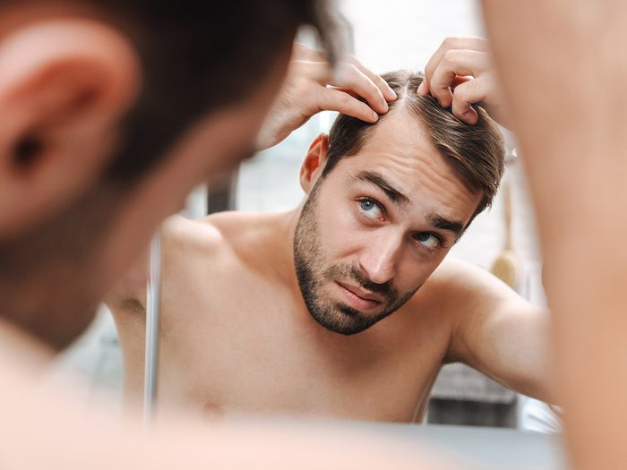 Signs you're not eating enough protein - man checking hair loss in mirror