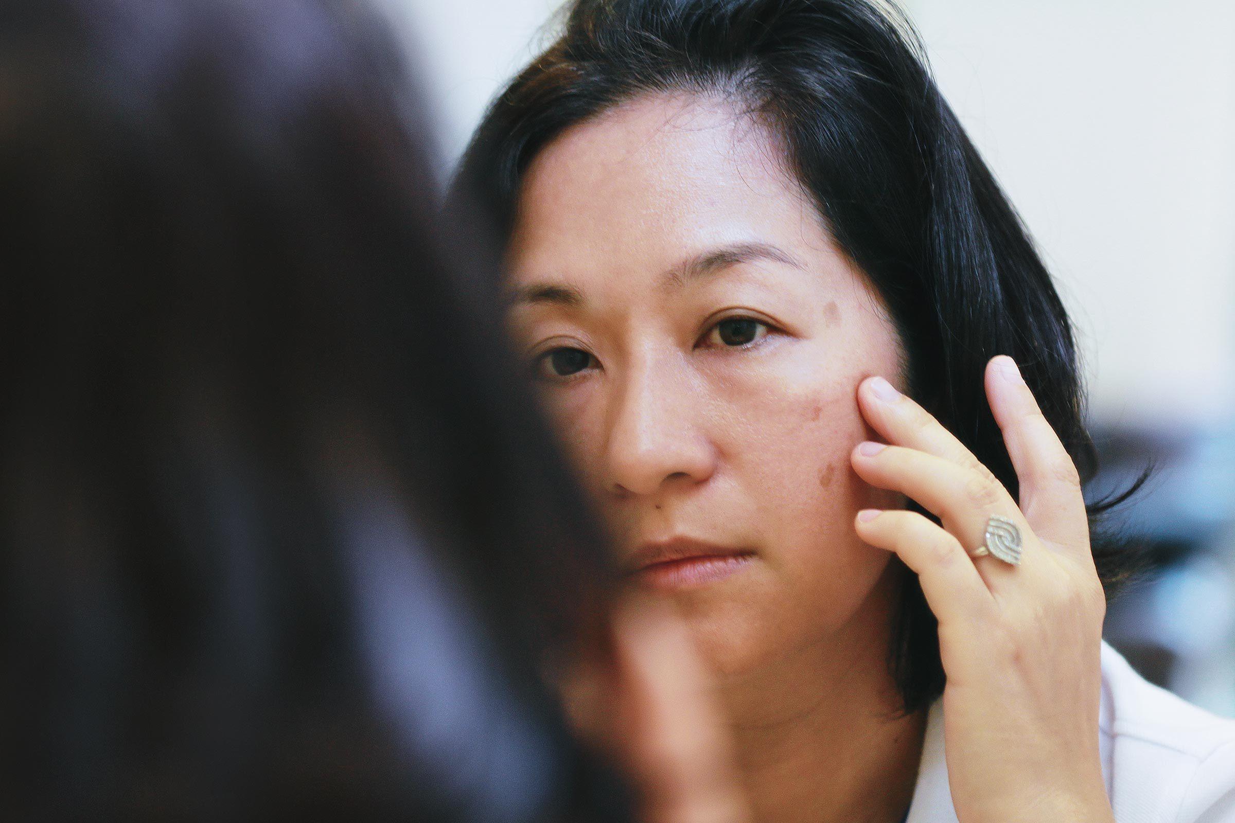 woman looking at face skin