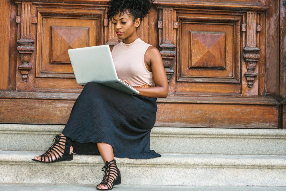 African American Student studying in New York, with afro hairstyle, wearing sleeveless light color top, black skit, strappy sandals, sitting by office door in New York, working on laptop computer.