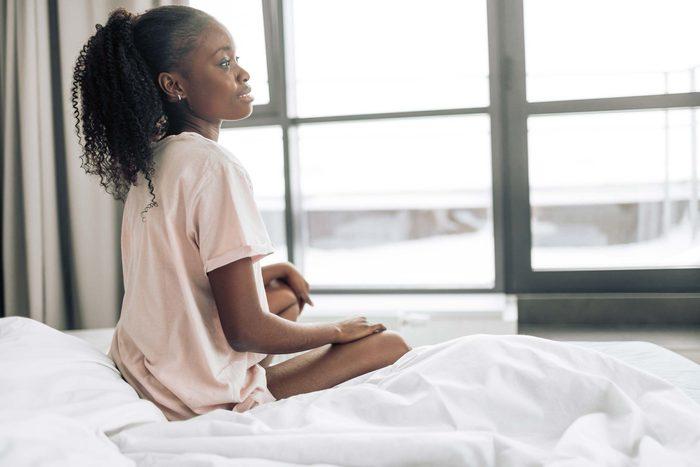 girl bed sitting window thinking