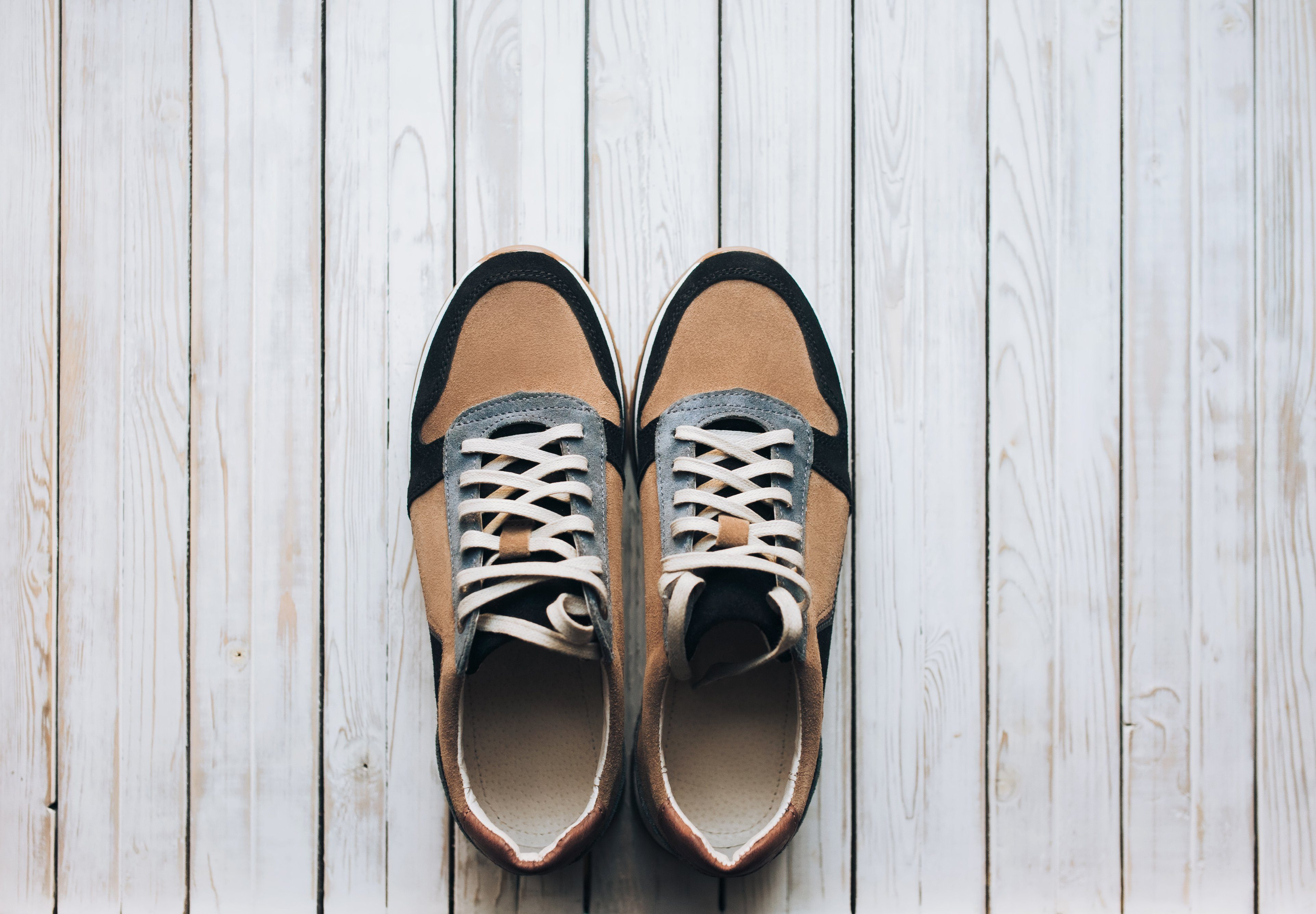 A pair of suede sneakers on a rustic wooden background. The concept of jog and sports shoes. Top view, copy space.