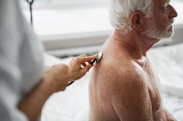 Side view portrait of shirtless bearded gentleman looking away during medical procedure. Female physician examining patient with stethoscope