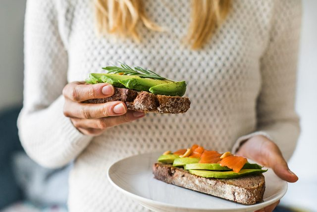 close up of woman holding plate with avocado toast as fresh snack, day light.