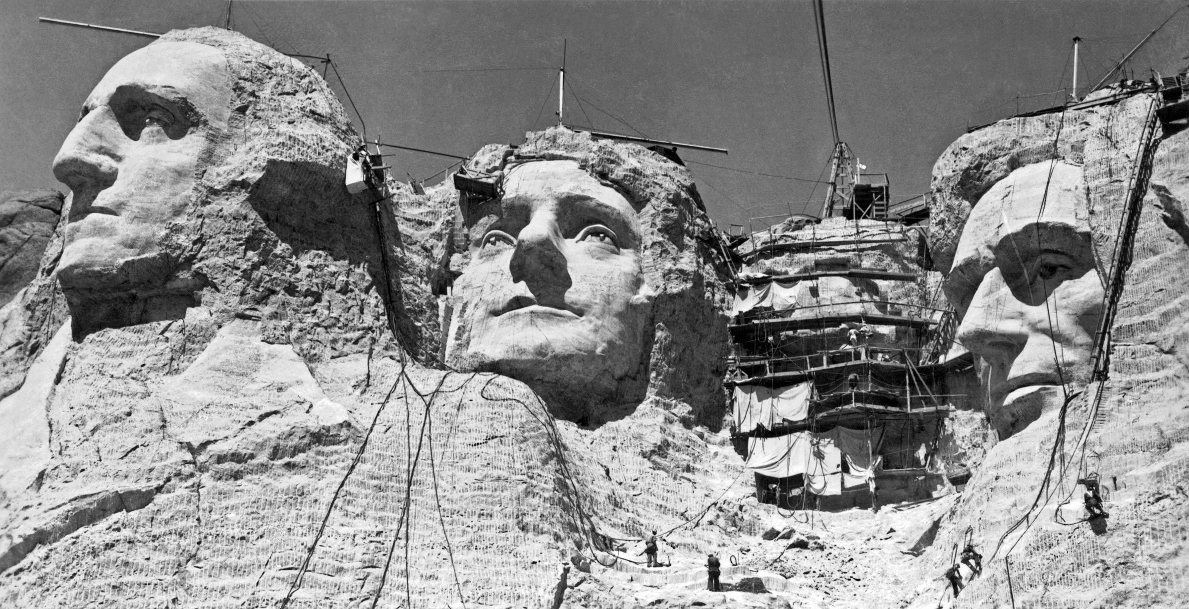 VARIOUS Mt. Rushmore, South Dakota: c. 1938. Workmen on the faces of Mount Rushmore. Roosevelt has the scaffolding over his face.