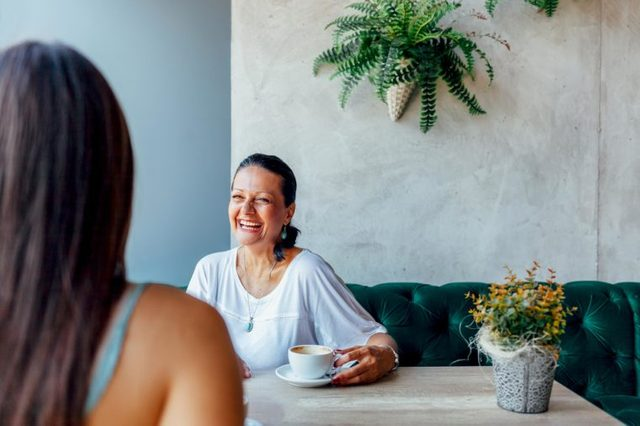 Two happy women talking in cafe. Aged woman and her adult daughter drinking coffee at cafe. Mothers day.