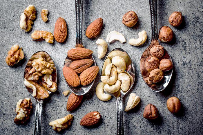 How to live to 100 - Walnuts, hazelnuts, almonds and cashew on metal silver spoons.