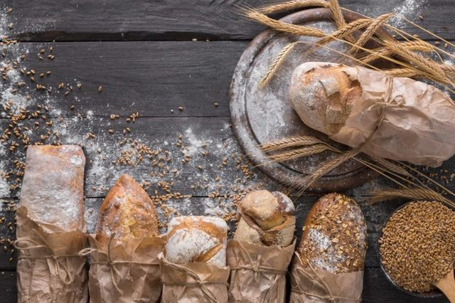 Bread background. Brown and white whole grain loaves wrapped in kraft paper composition on rustic dark wood with wheat ears scattered around. Baking and home bread making concept. Soft toning