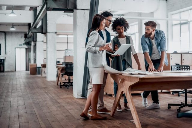Working through some concepts. Group of young business people working together in creative office while standing near the wooden desk