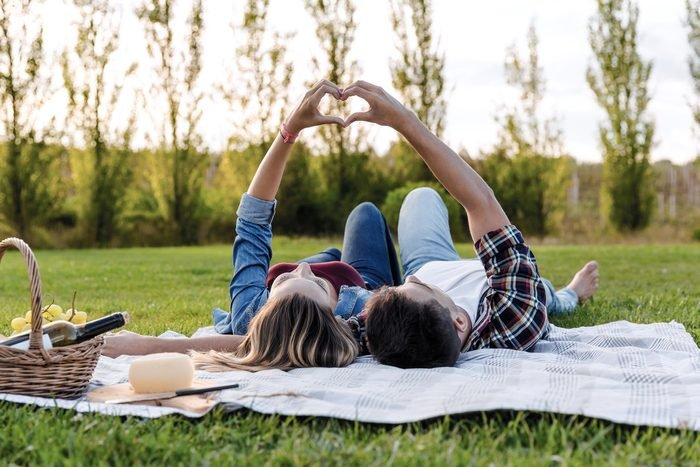 how to live to 100 - Happy couple in love, lying on the park and enjoying the day together