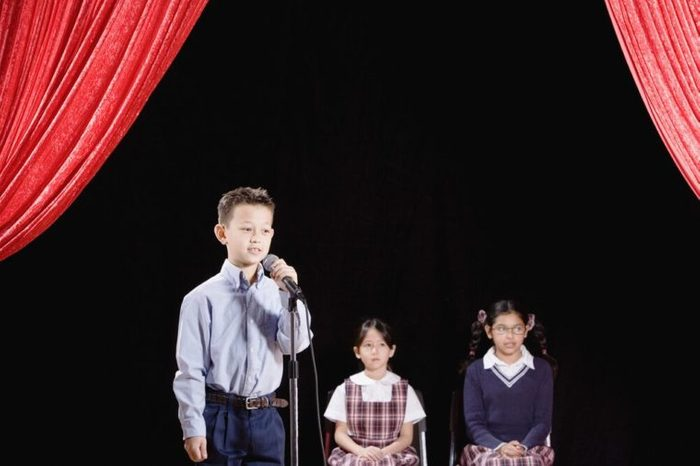 Asian boy speaking into microphone on stage