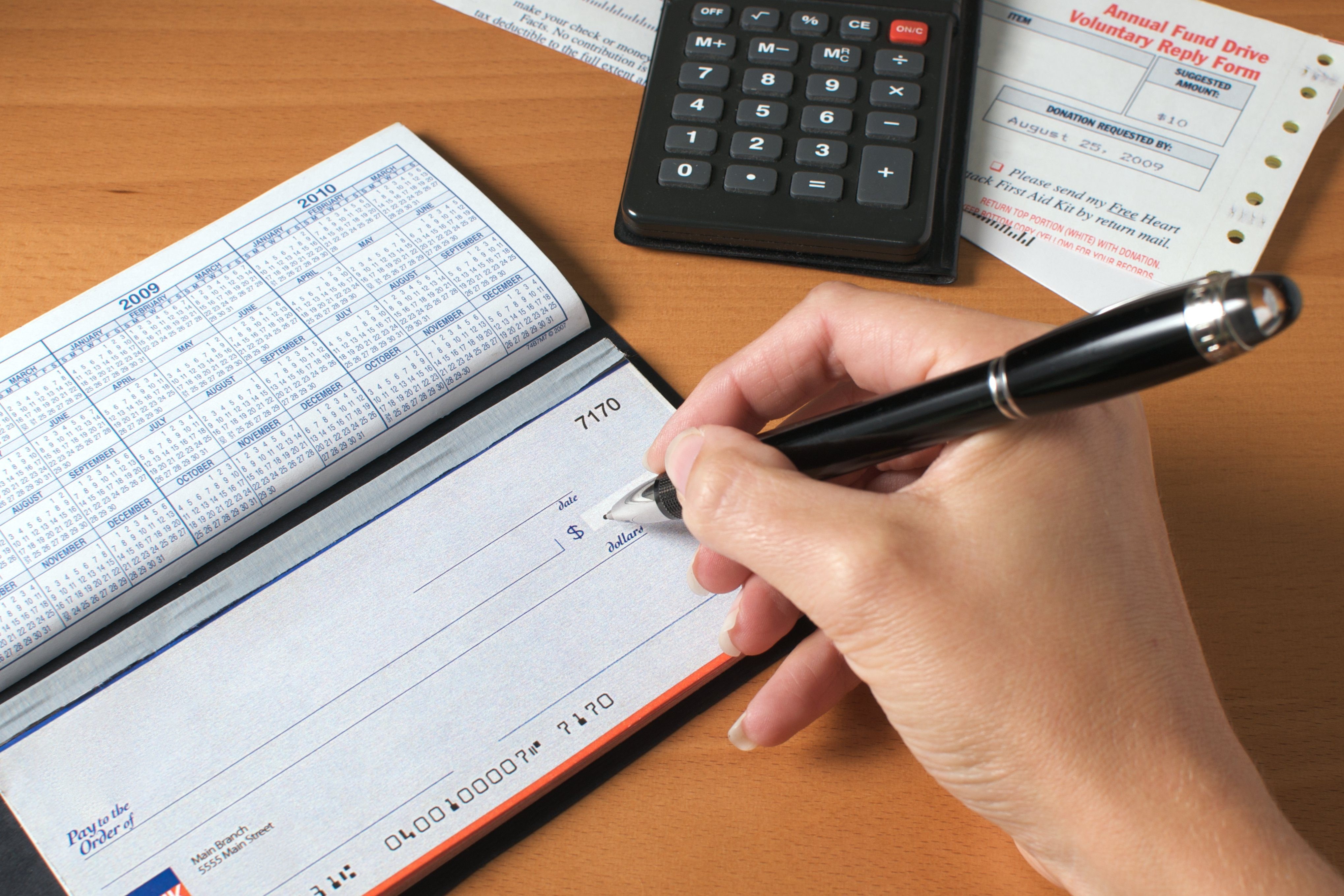 Woman's hand writing a check to pay the bills, with calculator and an invoice on the desktop.