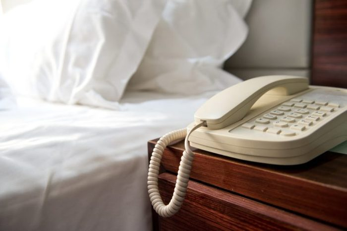 Phone on a table near a bed.