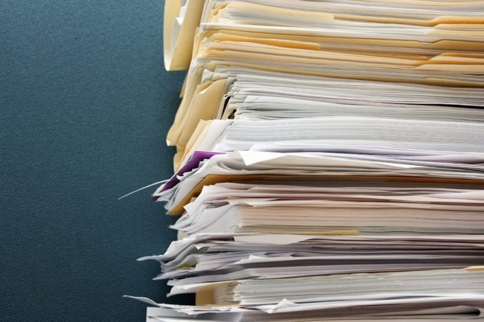 Pile of paperwork against a textured green cubicle wall