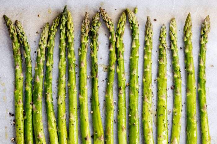 Asparagus spears on parchment paper over oven tray, ready for roasting. With olive oil and pepper.