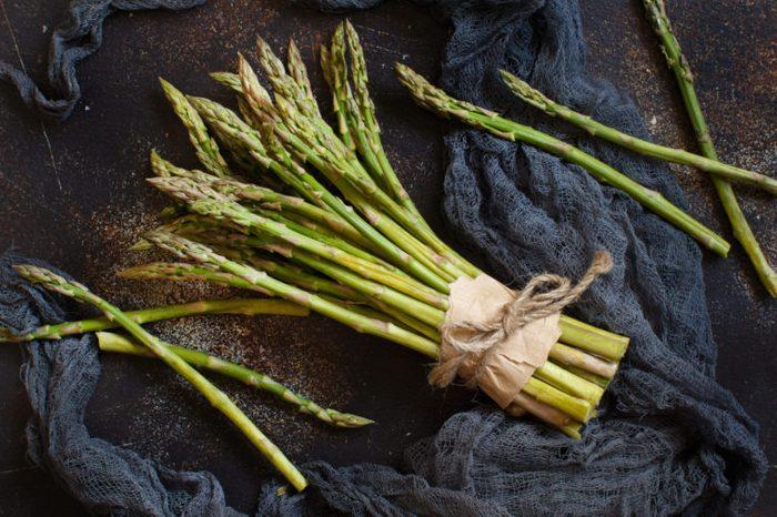 Fresh raw asparagus spears on a dark table