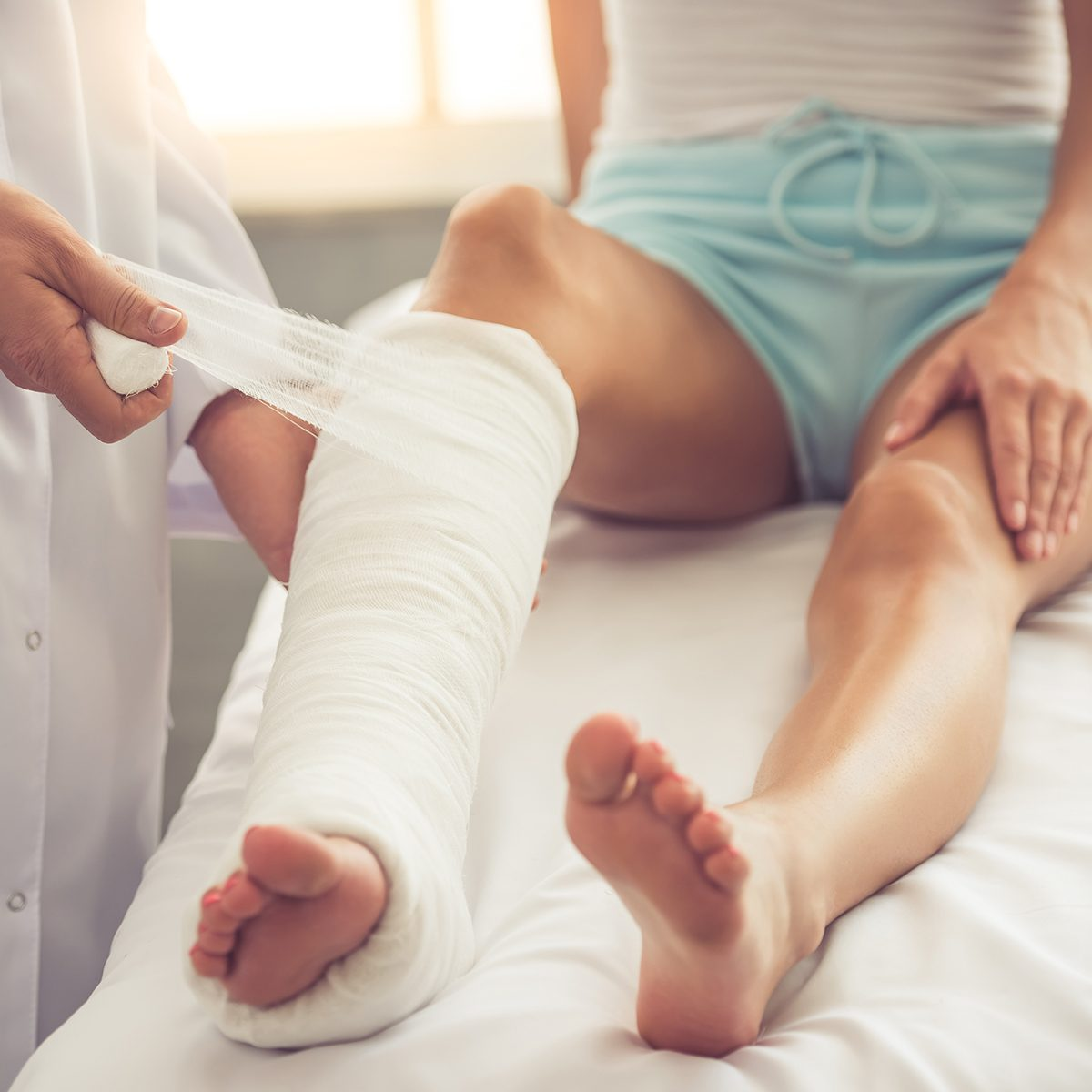Cropped image of handsome doctor bandaging woman's broken leg while working in his office