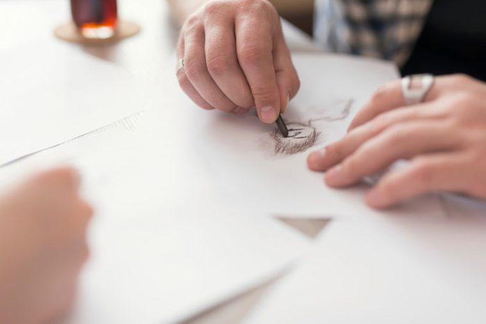 Close up of a young couple's hands, holding drawing charcoals and sketching on the empty sheets of paper. Leisure time activities,relaxation and spending quality time together