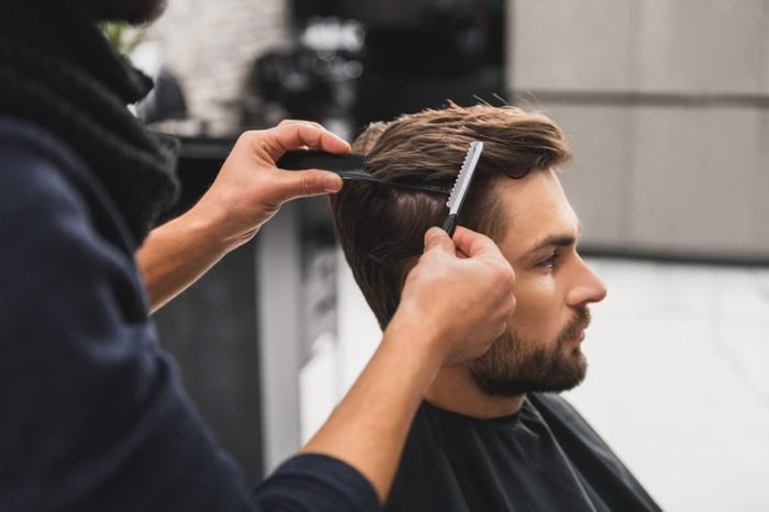 Male client getting haircut by hairdresser