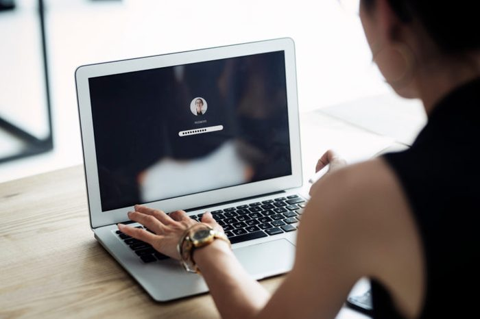 A woman is typing the password in her laptop computer. Communicate about privacy, passwords, security, business, working, data, anti-hacking, protection.