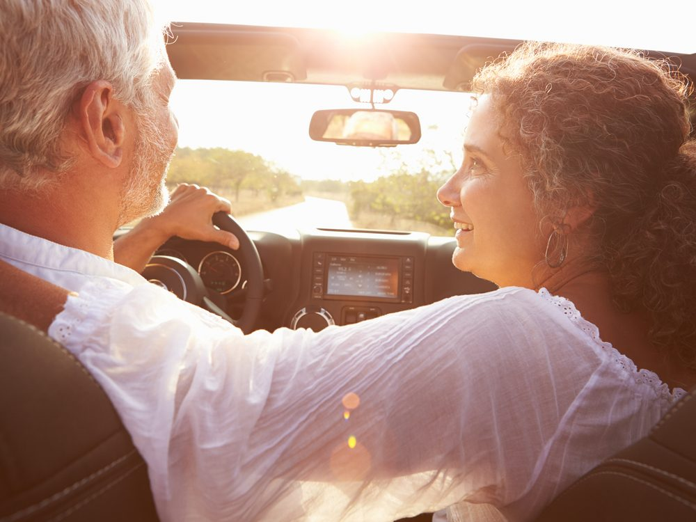Older couple driving in summertime