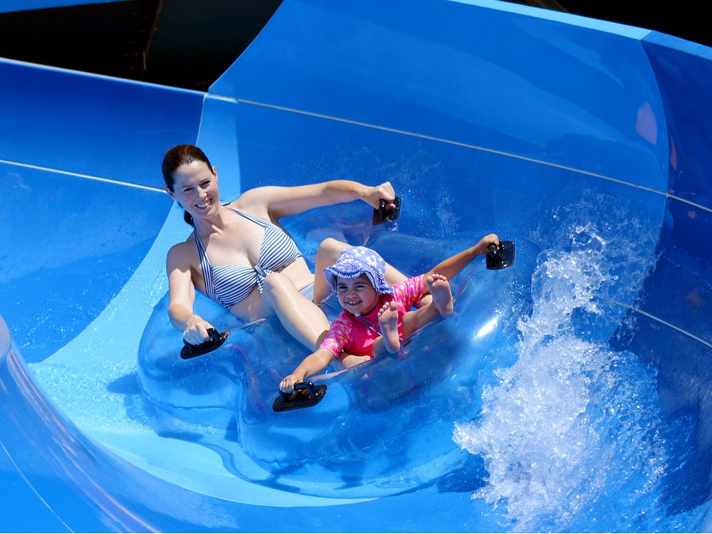 Mother and daughter having fun on water slide