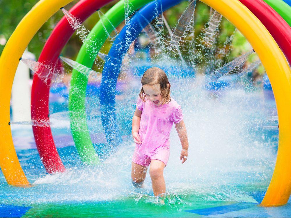 Toddler running through fountain at water park