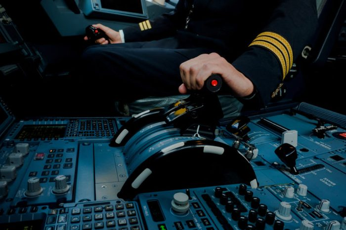 Captain hand accelerating on the throttle in commercial airplane