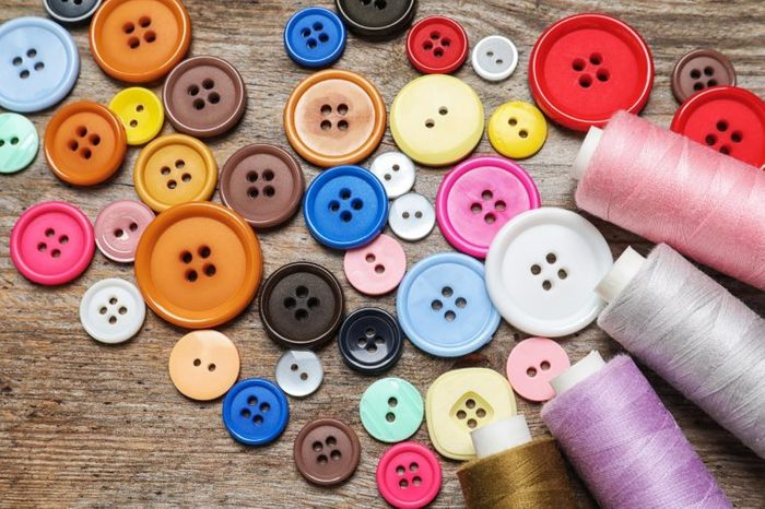 Colorful buttons and threads on wooden background, top view. Tailoring equipment