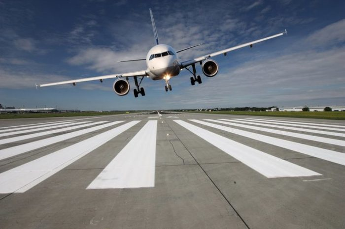 Landing aircraft low over the runway with stretched landing gear