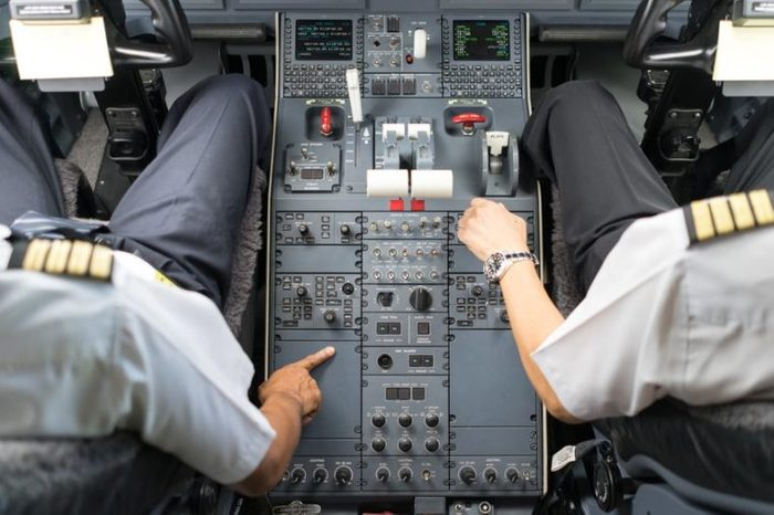 view of business jets cockpit. Two pilots operate a switches of aircraft system prior to departure.