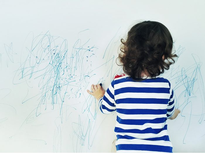 Little girl drawing on wall with crayons