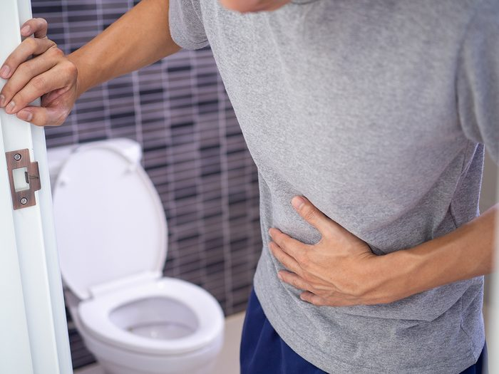 What your poop says about your health - man leaving bathroom just pooped