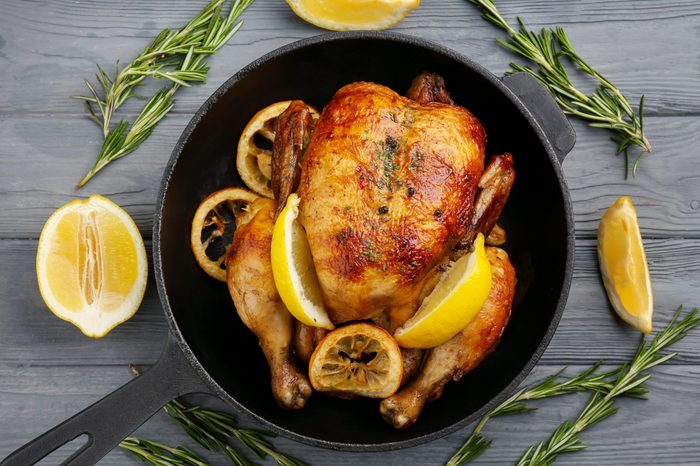 Homemade baked chicken with lemon on wooden background