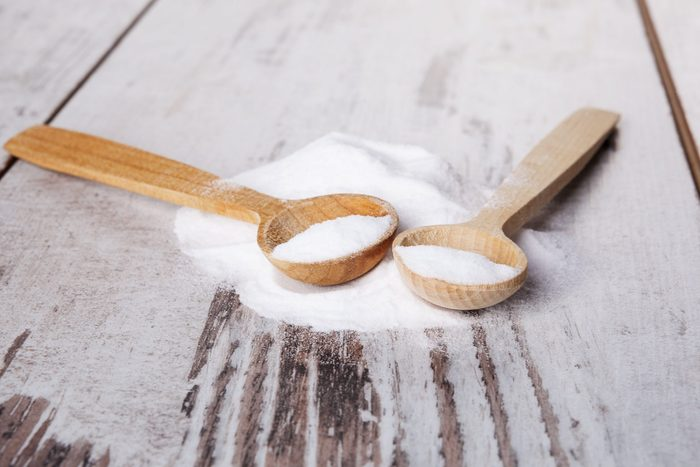 Baking soda on wooden spoon on white wooden textured background.