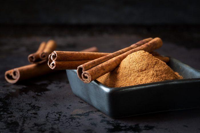 Ground cinnamon powder and cinnamon sticks in a black bowl on dark rustic background