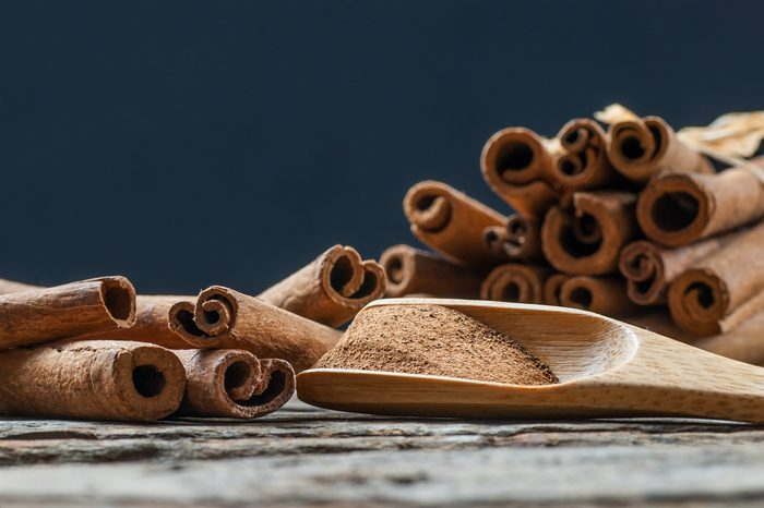 Close up cinnamon sticks and cinnamon powder in wooden spoon on wooden table background, healthy spice concept